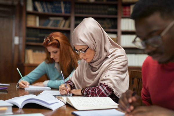 Focused student in hijab studying with classmates in university library. Islamic young woman in spectacles wearing abaya and writing in notebook. Arabian girl studying with multiethnic students sitting in a row.